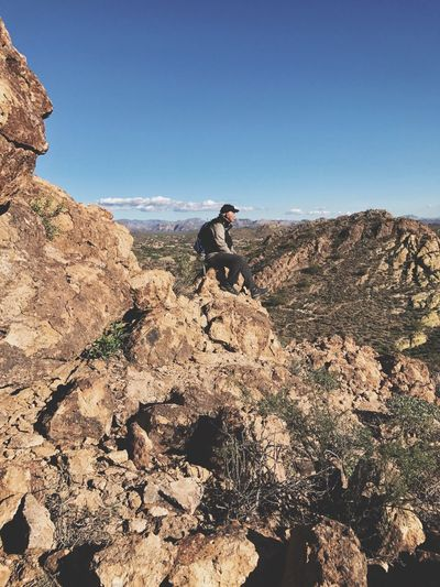 Man sitting on rocky mountain against clear sky