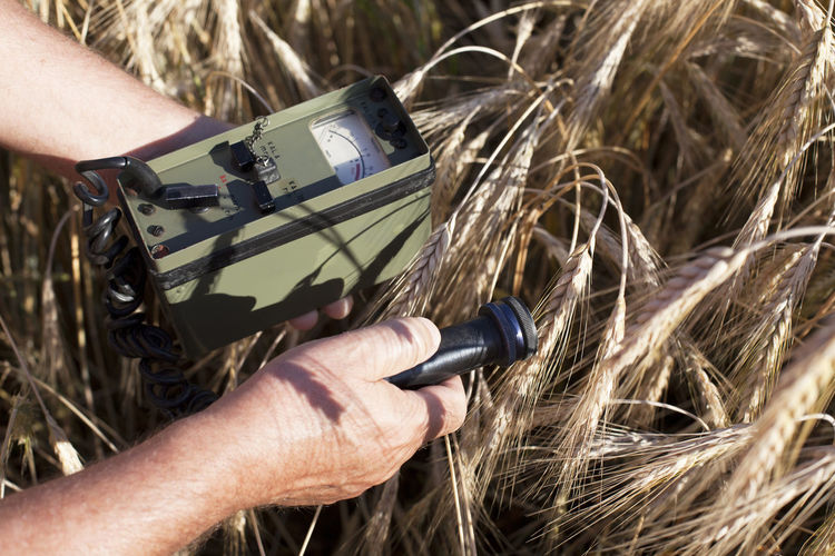Cropped image of man holding geiger counter on field
