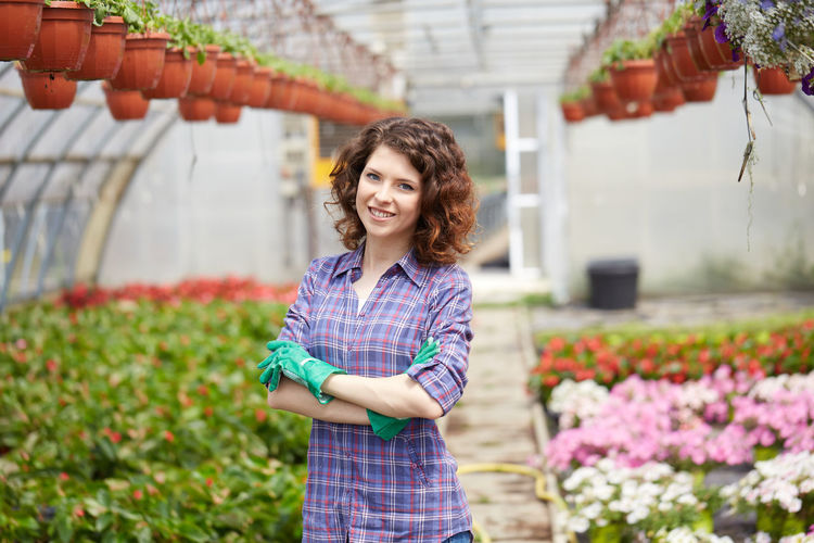 Portrait of young woman with arms crossed standing amidst plants in greenhouse