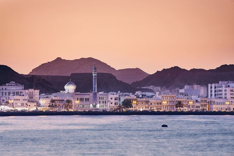 Skyline of Muscat city at golden sunset. The capital of Oman. Muscat Oman Skyline City Cityscape Sunset Building Exterior Built Structure Travel Travel Destinations Tourism Mosque Moody Sky Sky Mountain Water Sea Long Exposure Waterfront Nature Mountain Range Residential District Clear Sky Beauty In Nature Landscape