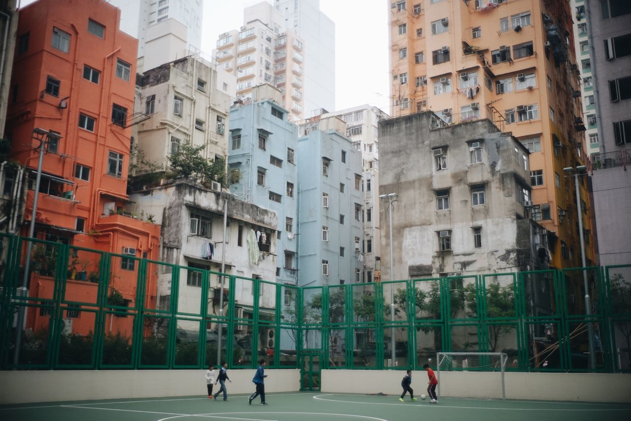 Boys playing soccer at court against buildings