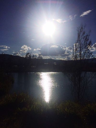 Scenic view of lake against bright sun