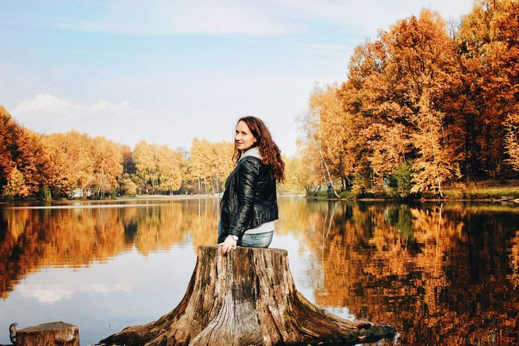 Woman standing by lake against trees during autumn