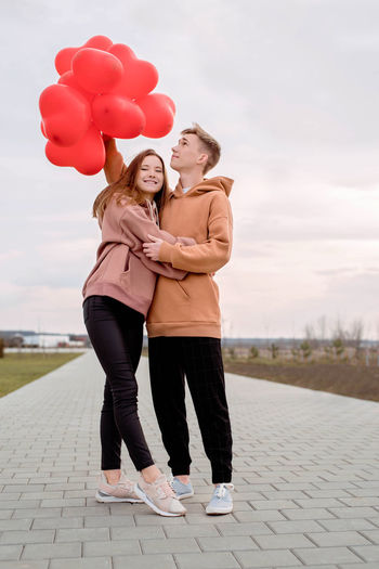 Valentines day. young loving couple hugging and holding red heart shaped balloons outdoors