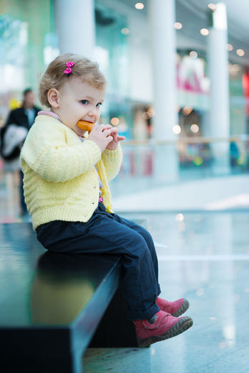Cute girl eating food while looking away while sitting at mall