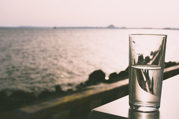Glass Of Water On Table Against Sea At Pomorie