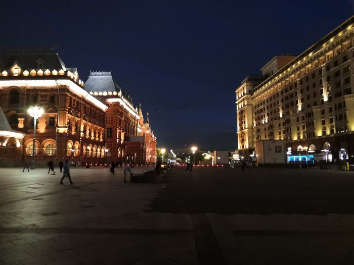 People on street amidst illuminated buildings in city at night