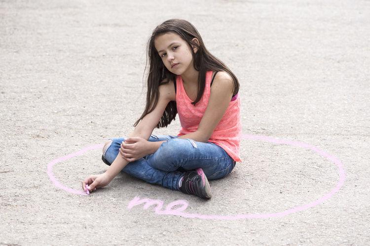 Portrait of girl sitting on street