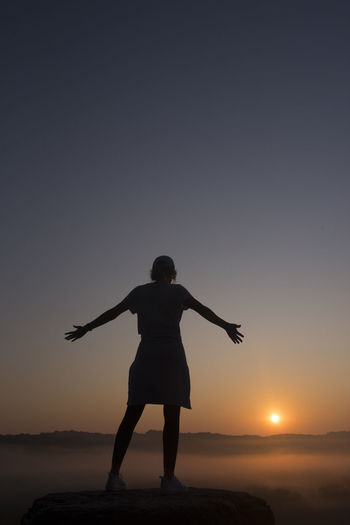 Rear view of silhouette person standing on land against sky during sunset