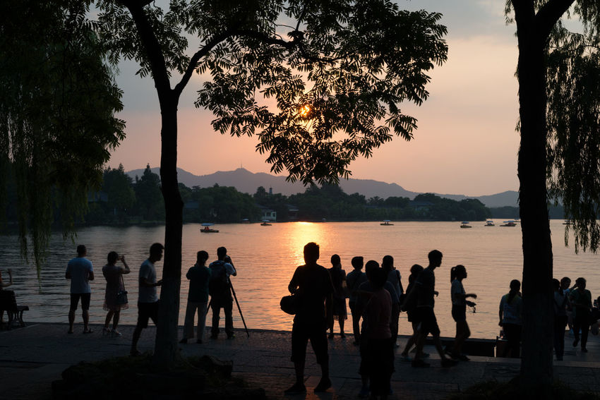 photographing the sunset - west lake hangzhou, zhejiang, china. people are drawn to the night sunset across the famous west lake. Daytime temperatures of 41Celcius draw people out at night to enjoy the slightly cooler temperatures and the charm of Hangzhou's west lake ASIA Hangzhou Reflection Silouette & Sky Todays News! China Cooler At Night High Temperatures People Doing Thing Photographing Sunset