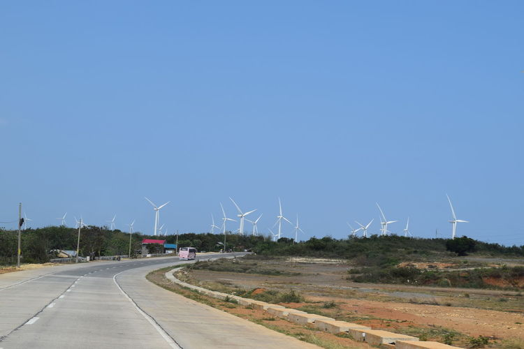 Windmills on field against clear blue sky