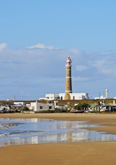 Lighthouse by sea against buildings against sky