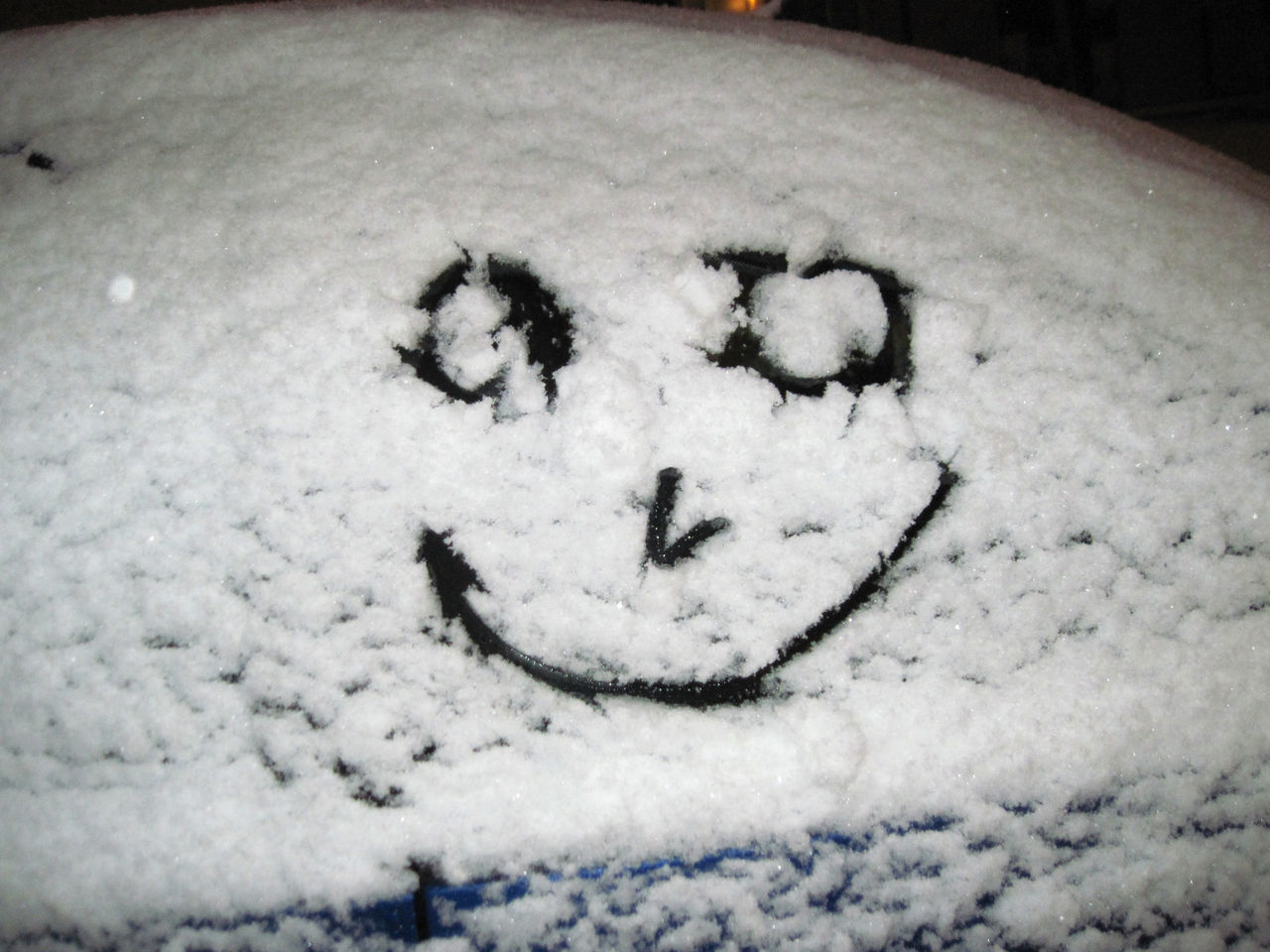 Smiley Face On Snow Covered Car Window