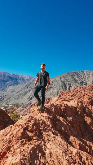 Full length of man on rock against clear blue sky