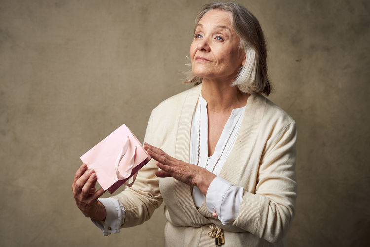 Midsection of woman holding paper while standing against wall