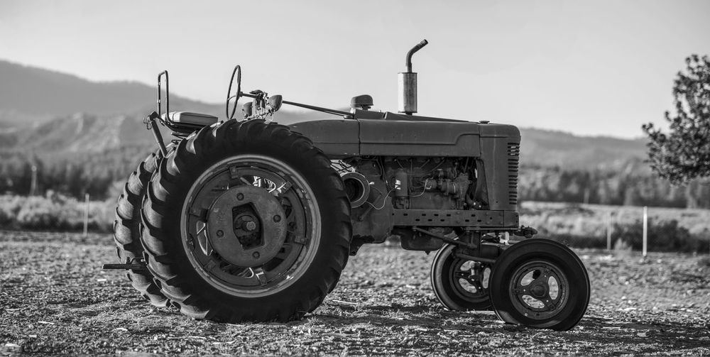 Close-up of tractor on field against clear sky