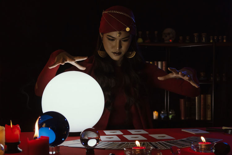 Female fortune teller with sphere and tarot cards at home