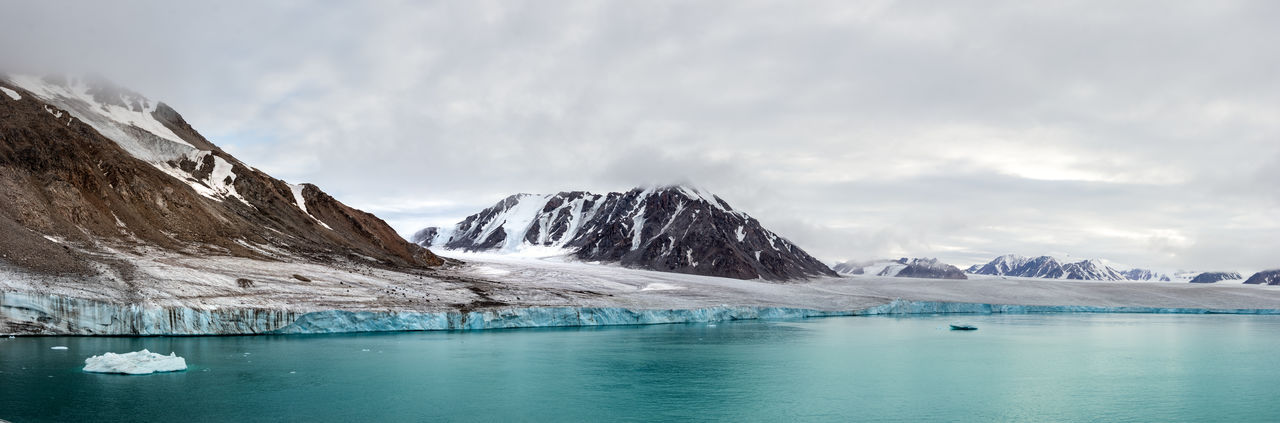 Scenic view of glacier against mountain during winter in the canadian arctic.