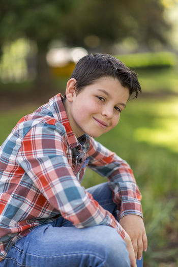 portrait of a casual teen boy, outdoors Casual Clothing One Person Leisure Activity Three Quarter Length Focus On Foreground Sitting Checked Pattern Portrait Real People Lifestyles Day Looking At Camera Young Adult Young Men Smiling Front View Nature Men Outdoors Teenager Plaid Shirt  Jeans Teenage Boys