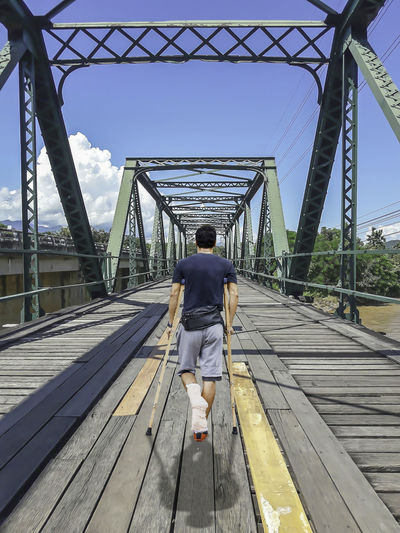 Rear view of disabled man walking with canes on footbridge