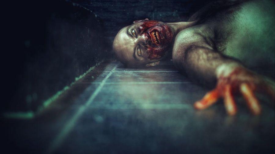 Portrait of zombie lying on floor