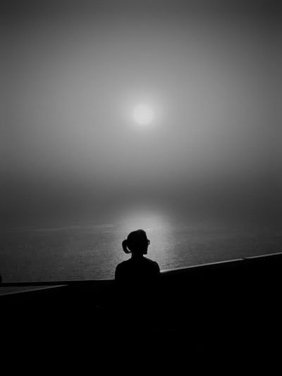 Silhouette man sitting by sea against clear sky during sunset