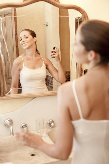 young attractive tourist single woman in spain Bathroom Bathroom Sink Beautiful Woman Body Care Day Domestic Bathroom Domestic Life Domestic Room Focus On Background Holding Home Interior Human Hand Indoors  Lifestyles Mirror One Person One Young Woman Only Perfume Preparation  Real People Reflection Standing Vanity Young Adult Young Women