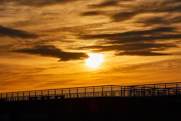 Silhouette bridge against dramatic sky during sunset