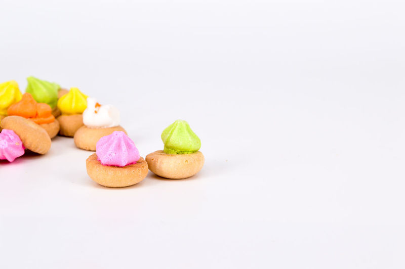 Close-Up Of Multi Colored Cookies On White Background