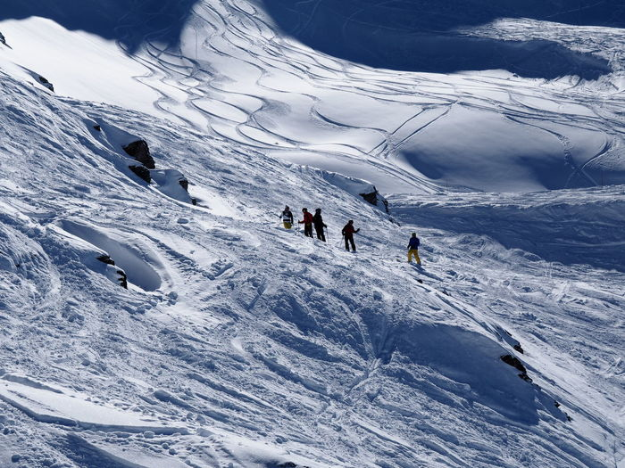 Tourists on snow covered mountain
