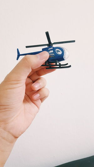 Action Figures Close-up Cropped Day Diecast Figure Helicopter Holding Human Finger Leisure Activity Lifestyles Optical Illusion Outdoors Part Of Person Photography Themes Smart Phone Toy Unrecognizable Person