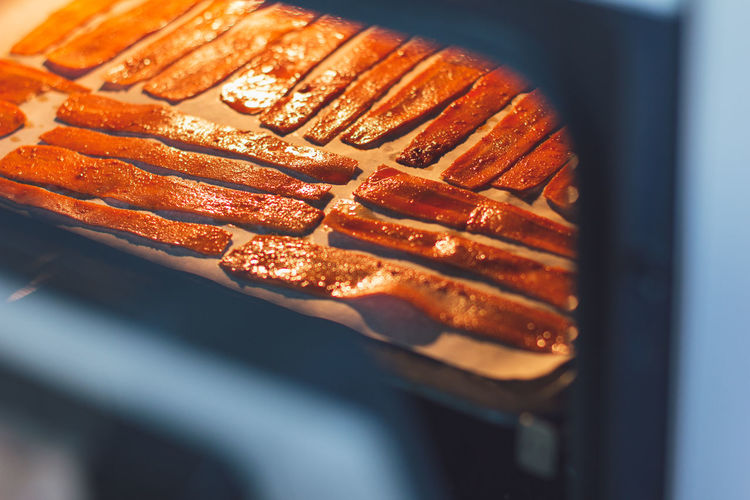 Sliced carrots in the oven on a protvin for cooking carrot bacon. vegetarian food, meat replacement