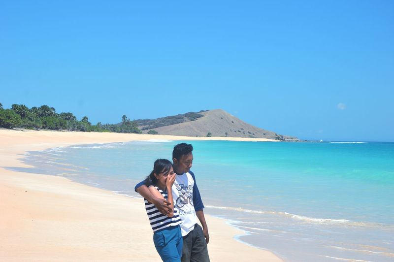 Young couple standing at beach against clear blue sky