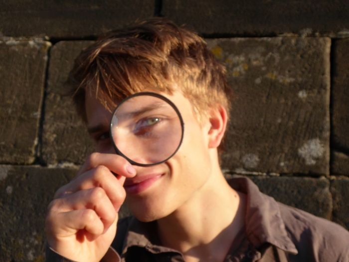 Portrait of smiling young man looking through magnifying glass against wall