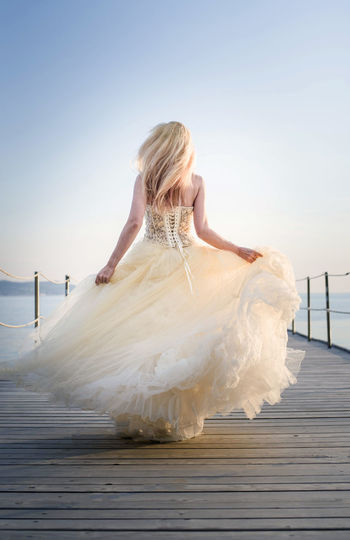 wedding time Wedding Wedding Photography Adult Beautiful Woman Blond Hair Clear Sky Clothing Dress Fashion Full Length Hair Hairstyle Leisure Activity Lifestyles Long Hair One Person Real People Rear View Sky Wedding Ceremony Wedding Day Wind Women Young Adult Young Women