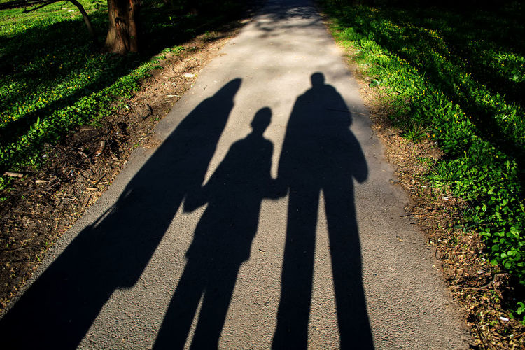 Shadow of parents with son on road