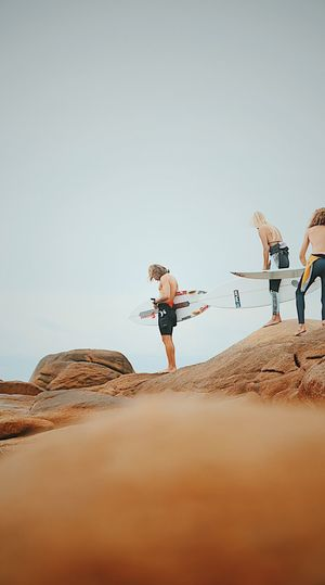 Man And Women With Surfboards Standing On Rock Formation Against Clear Sky