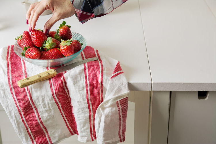 Cropped Hand Of Woman Taking Strawberry From Bowl On Table