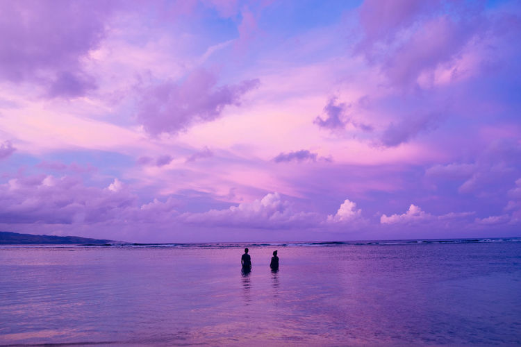 Silhouette couple standing in sea against purple sky during sunset