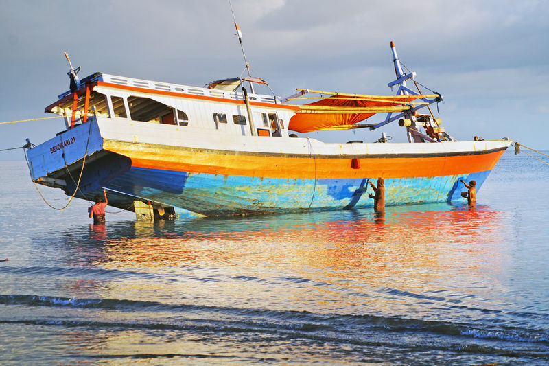 Fishing boat on beach against sky