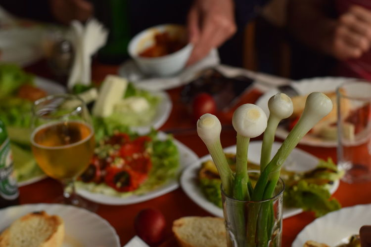 Spring onions in glass with food in plates on table
