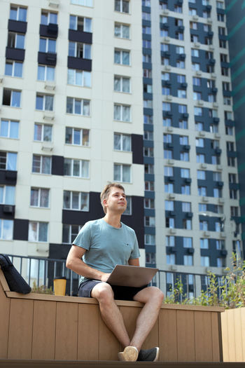 Young man sitting against building in city