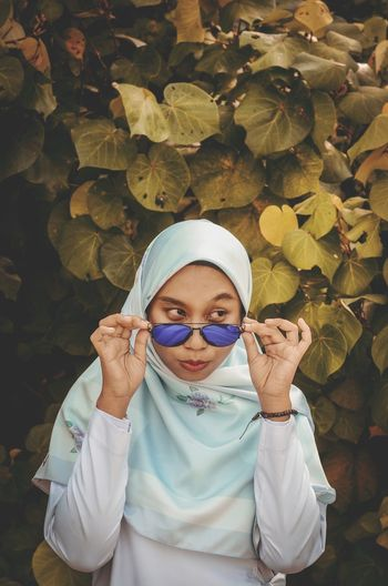 Young woman in hijab wearing sunglasses against leaves