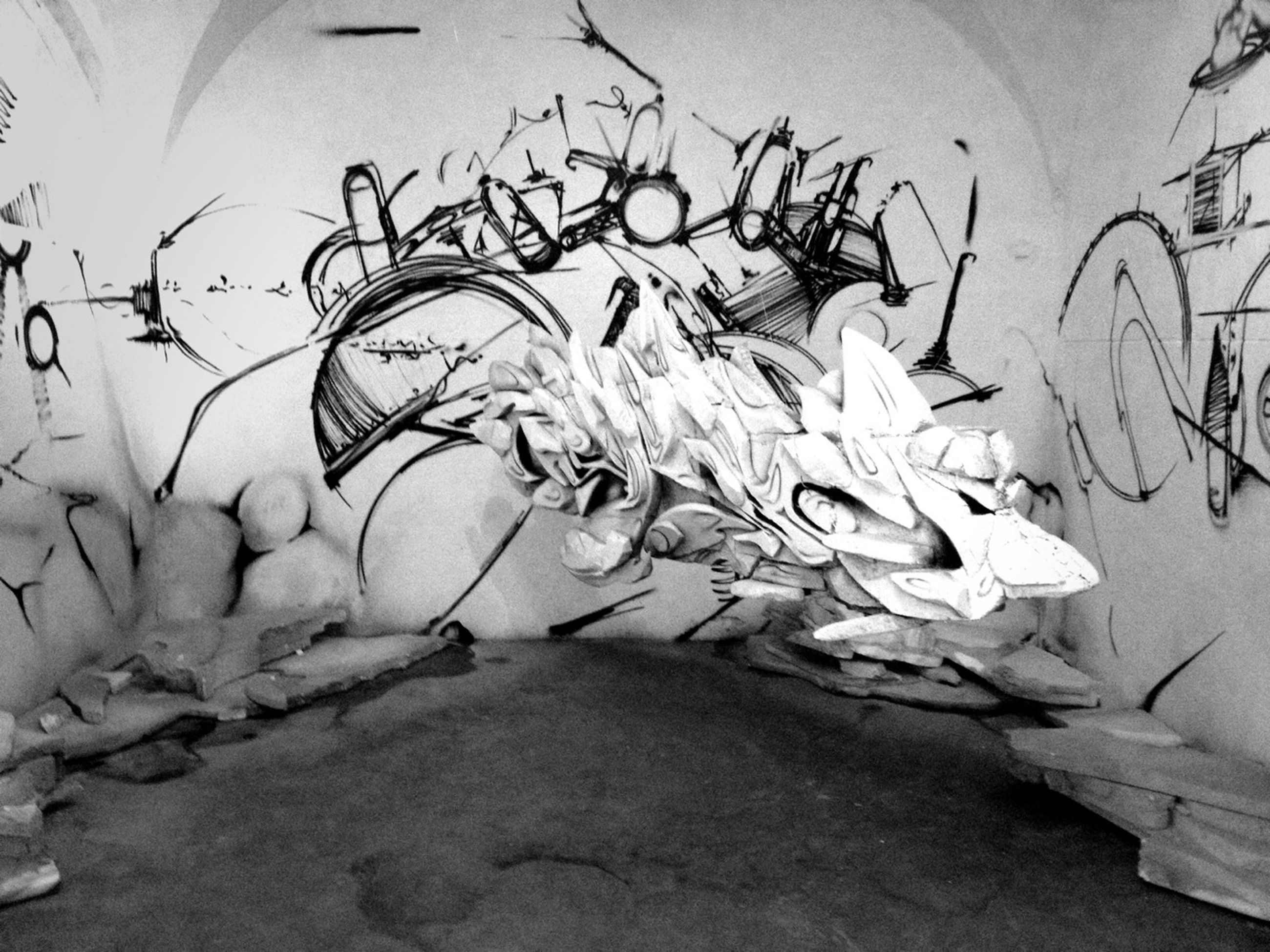 indoors, text, art and craft, art, creativity, wall - building feature, western script, communication, built structure, graffiti, architecture, human representation, no people, close-up, day, high angle view, wall, old, non-western script