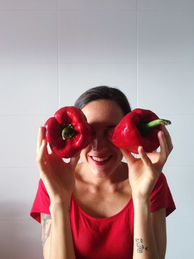 Woman holding red capsicum as eyes at home