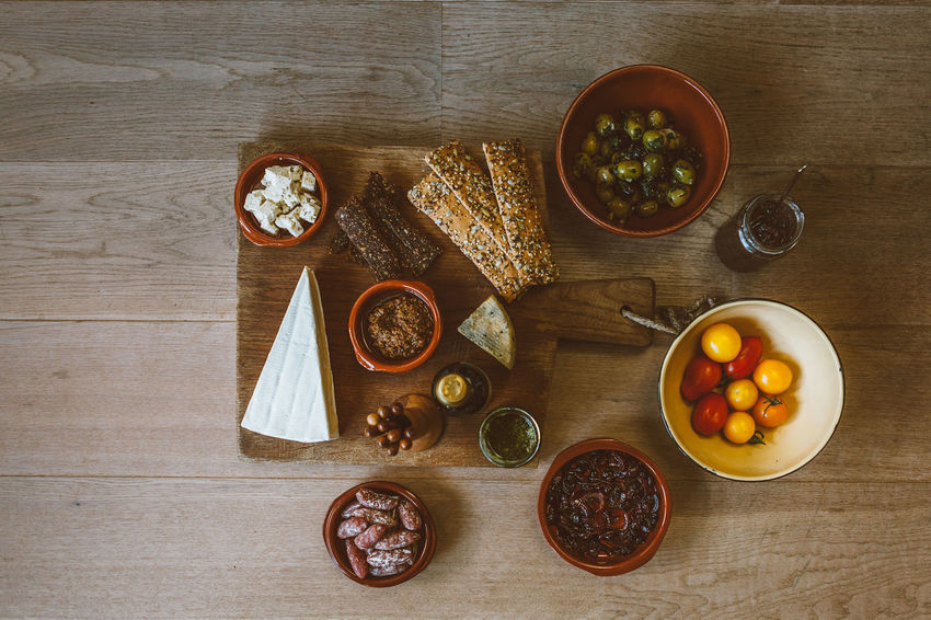 high angle view of a settled food party table Party Food Ready To Eat Tapas Appetizer Bowl Breakfast Cherry Tomatoes Crackers Cutting Board Cutting Boards Day Directly Above Food Food And Drink Freshness Fruit Healthy Eating High Angle View Indoors  No People Olive Olives Salami Spread Table