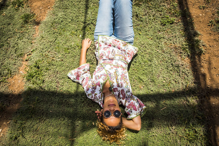 High Angle View Of Mature Woman Lying On Grassy Field During Sunny Day