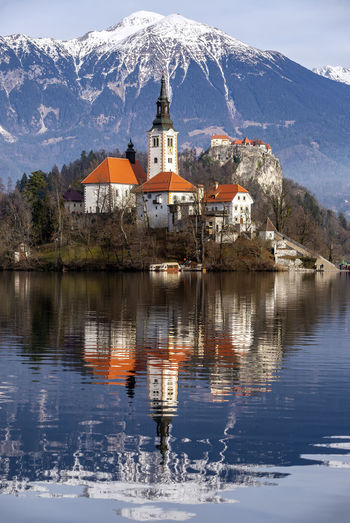 Reflection of chapel in lake against snowcapped mountain