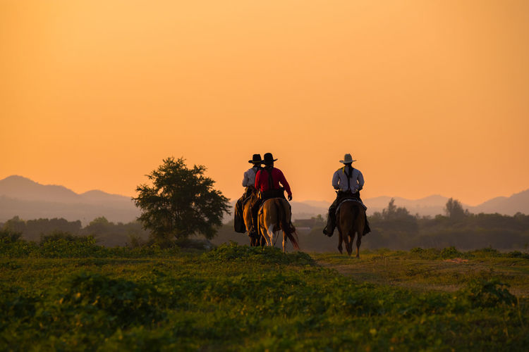 People riding horse on field against sky during sunset