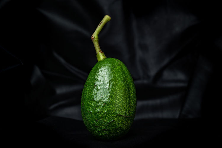 Close-up of green lemon on table against black background